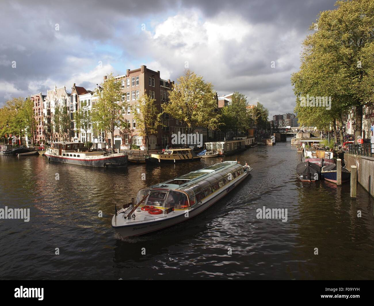 Ferryboats at canal with canal houses in background, Amsterdam, Netherlands - Stock Image
