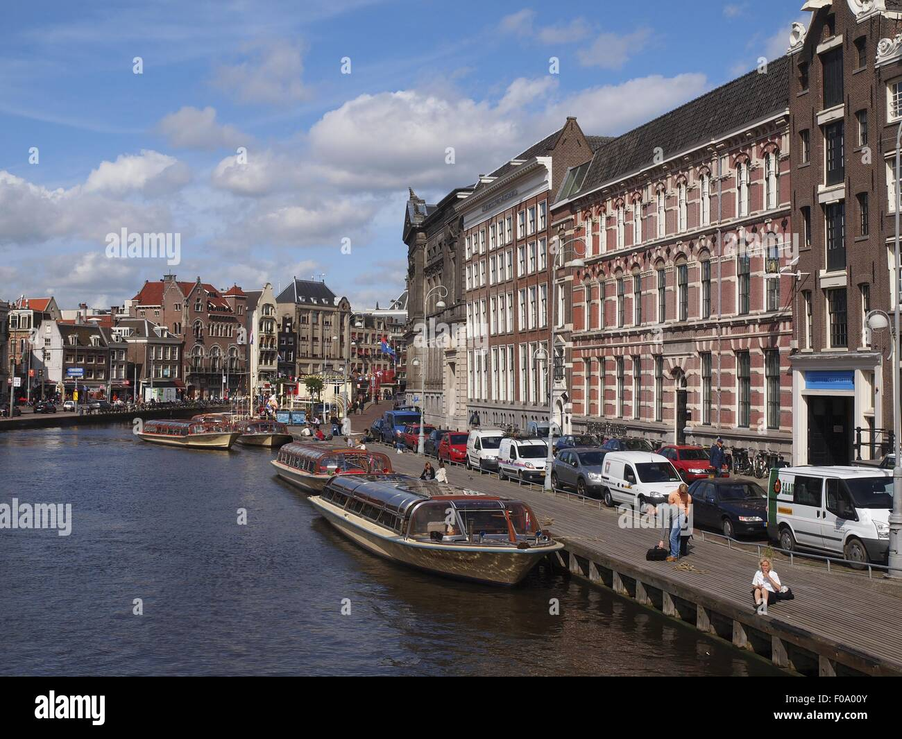 View of canal houses and ferryboats in canal Amsterdam at Nieuwmarkt, Netherlands - Stock Image