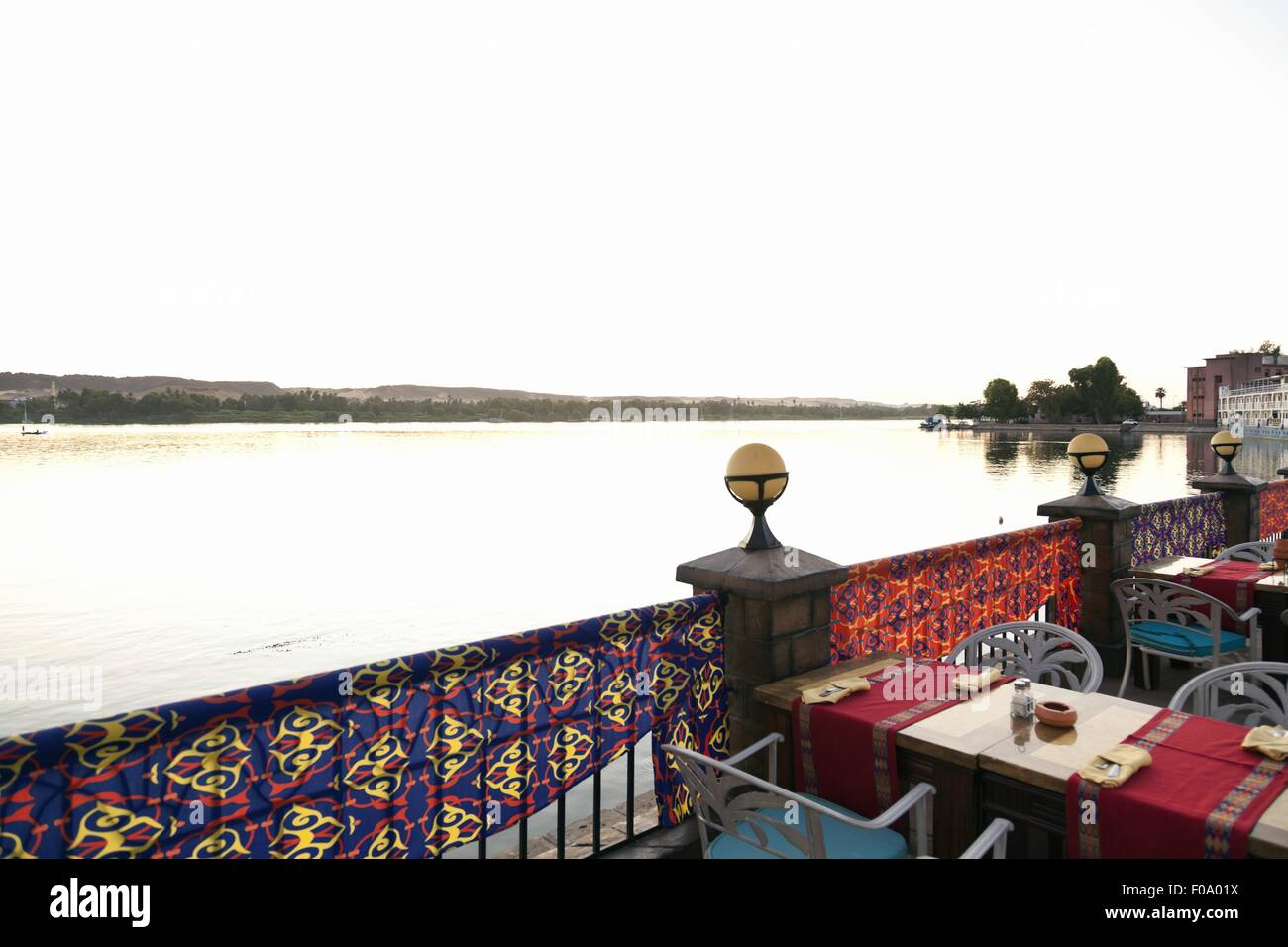 View of river and table laid on the terrace of Aswan Hotel, Aswan, Egypt - Stock Image