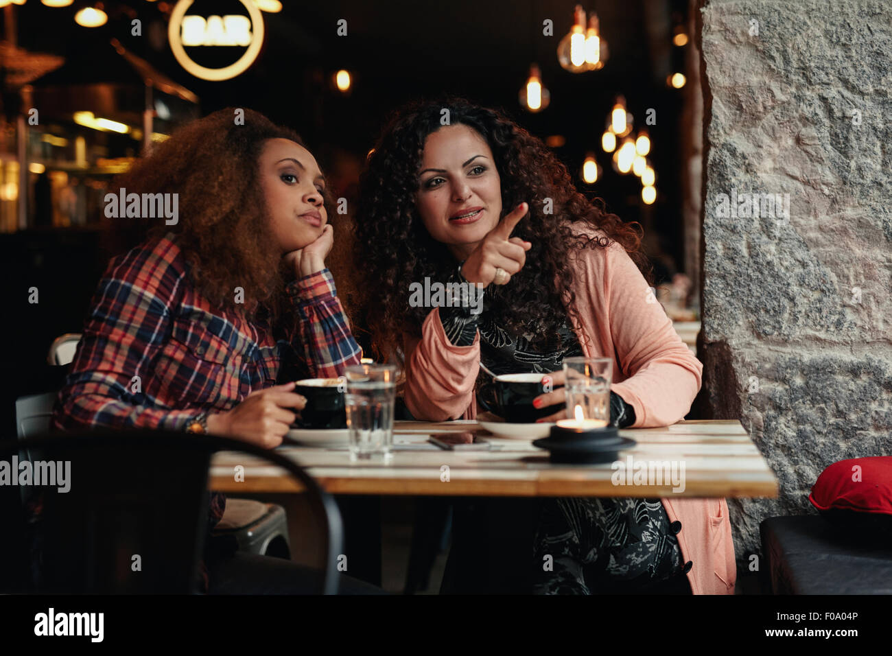 Two young women sitting at a restaurant looking away, with one pointing away showing something to her friend. - Stock Image