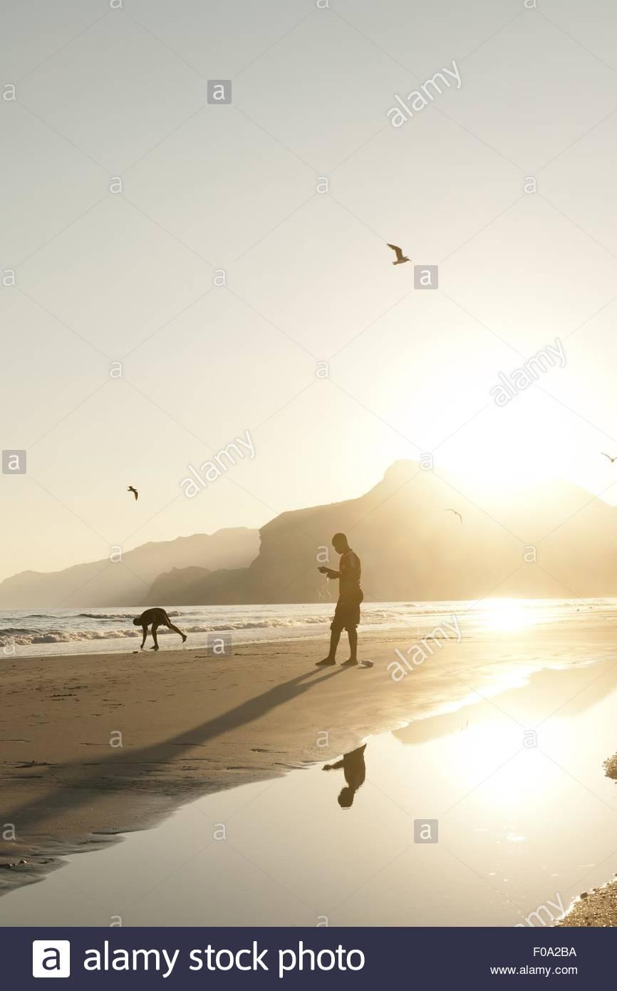 People fishing on Maghsail Bay Beach at sunrise in Salalah