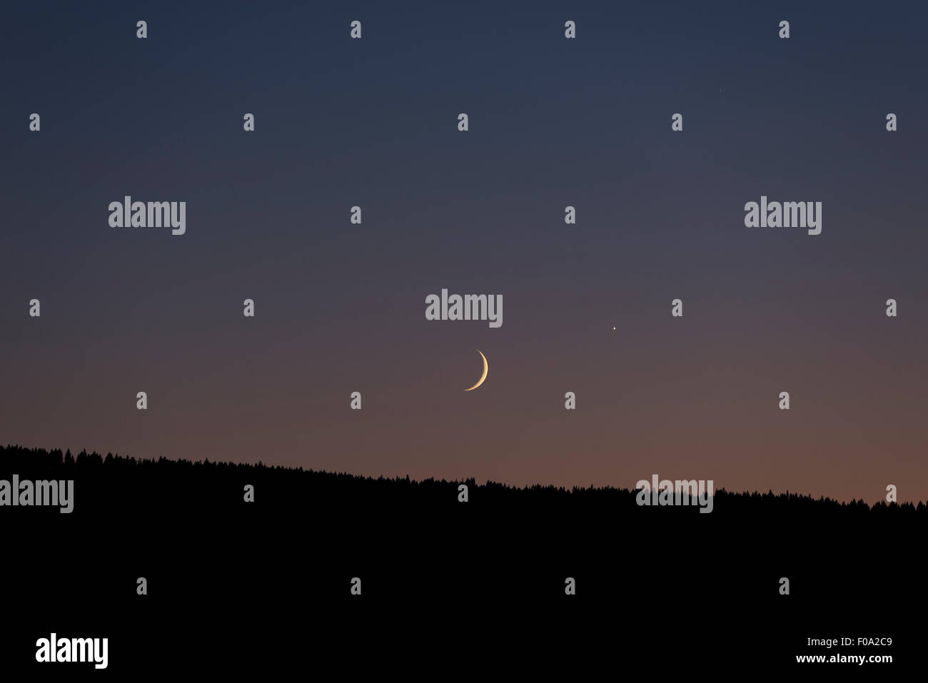 Crescent moon setting over the Wallowa Mountains at dusk, Oregon. - Stock Image