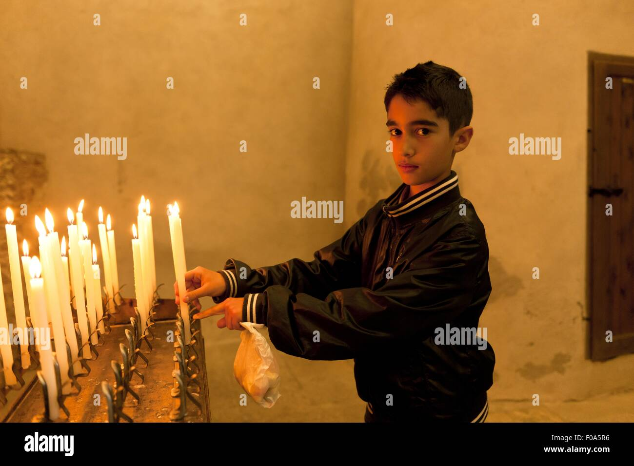 Side view of boy placing candle in church, Nora, Sardinia, Italy - Stock Image