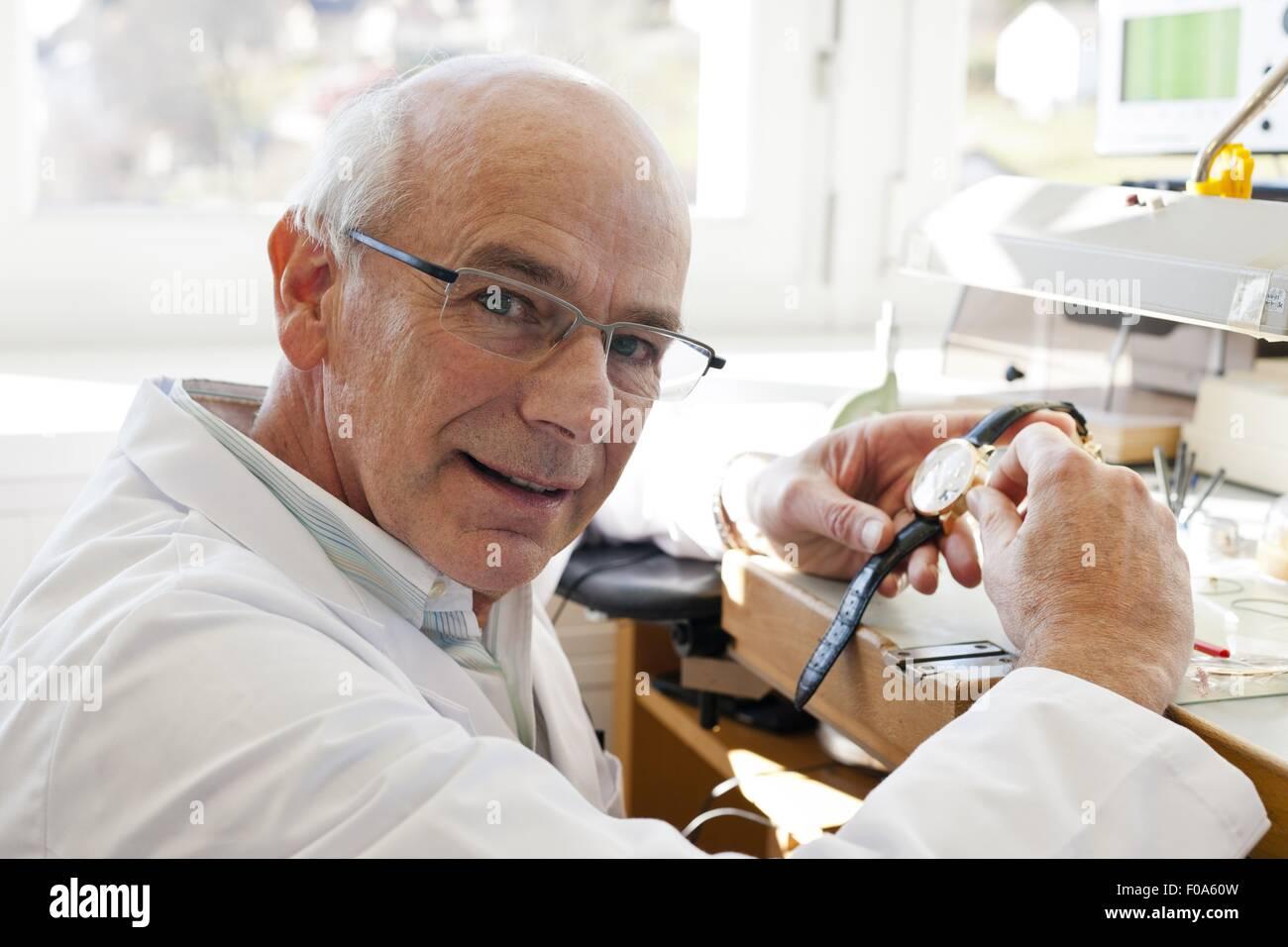 Senior man repairing a watch, Le sentier, Vallee de Joux, Switzerland - Stock Image