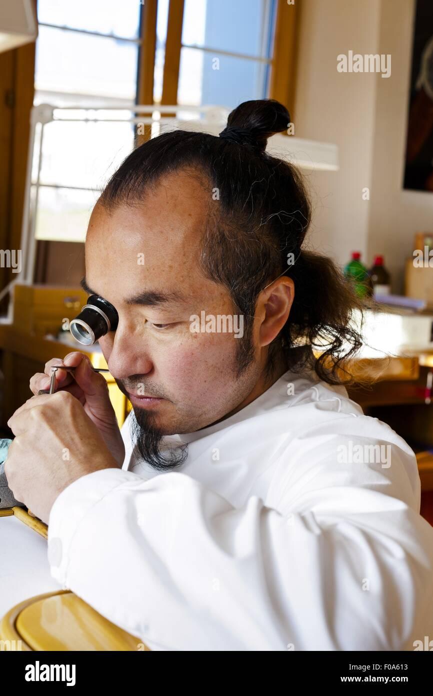 Man working with lens, Le Soliat, Vallee de Joux, Switzerland - Stock Image