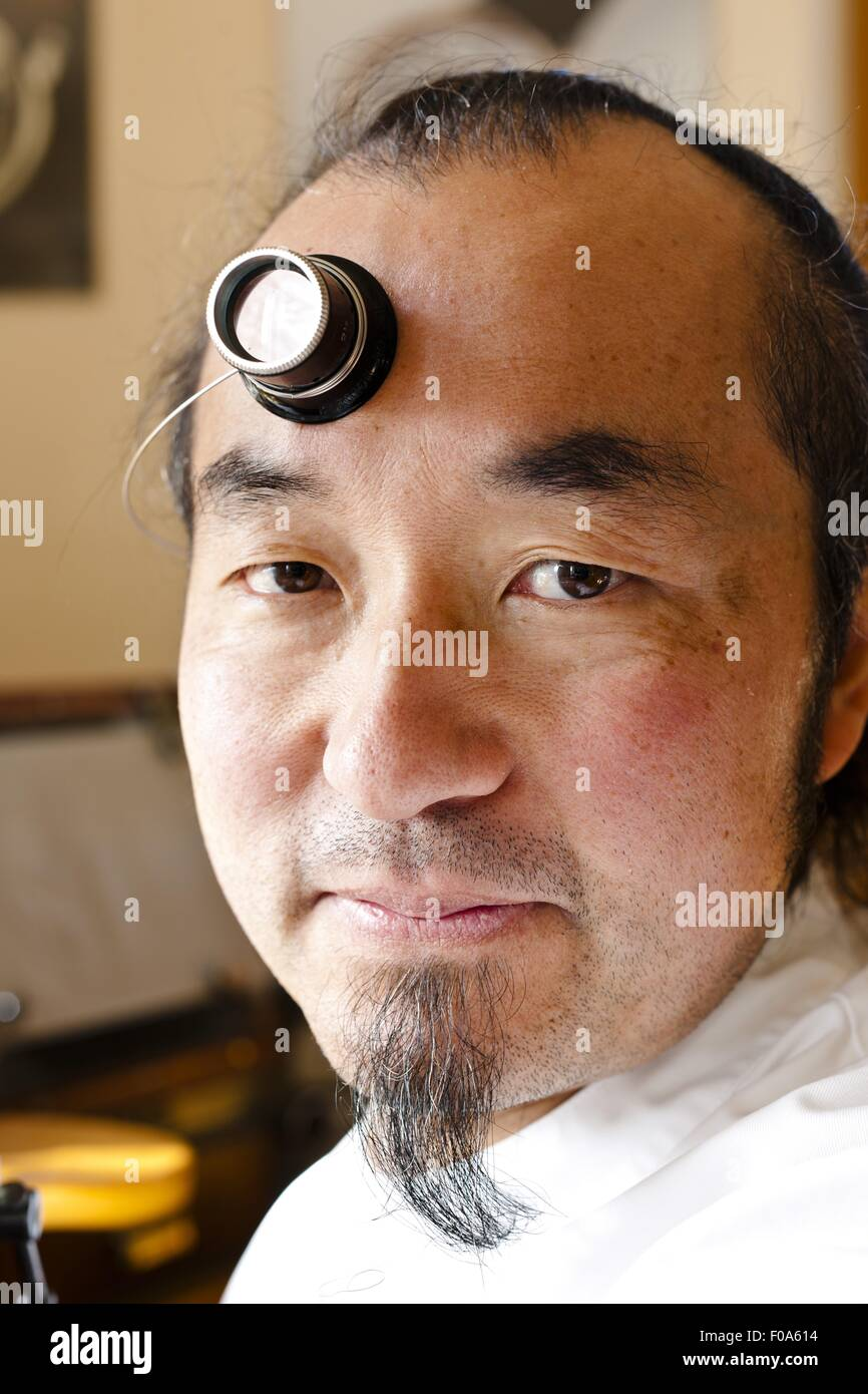 Man wearing magnifying glass on forehead, Le Soliat, Vallee de Joux, Switzerland - Stock Image