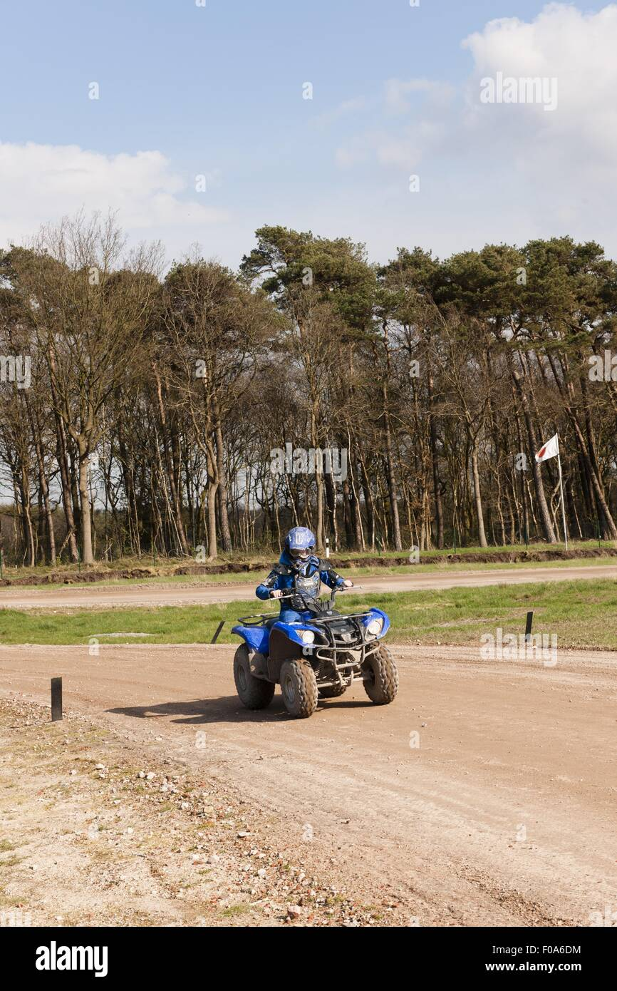 Boy riding razor blue quad dirt bike in forest - Stock Image