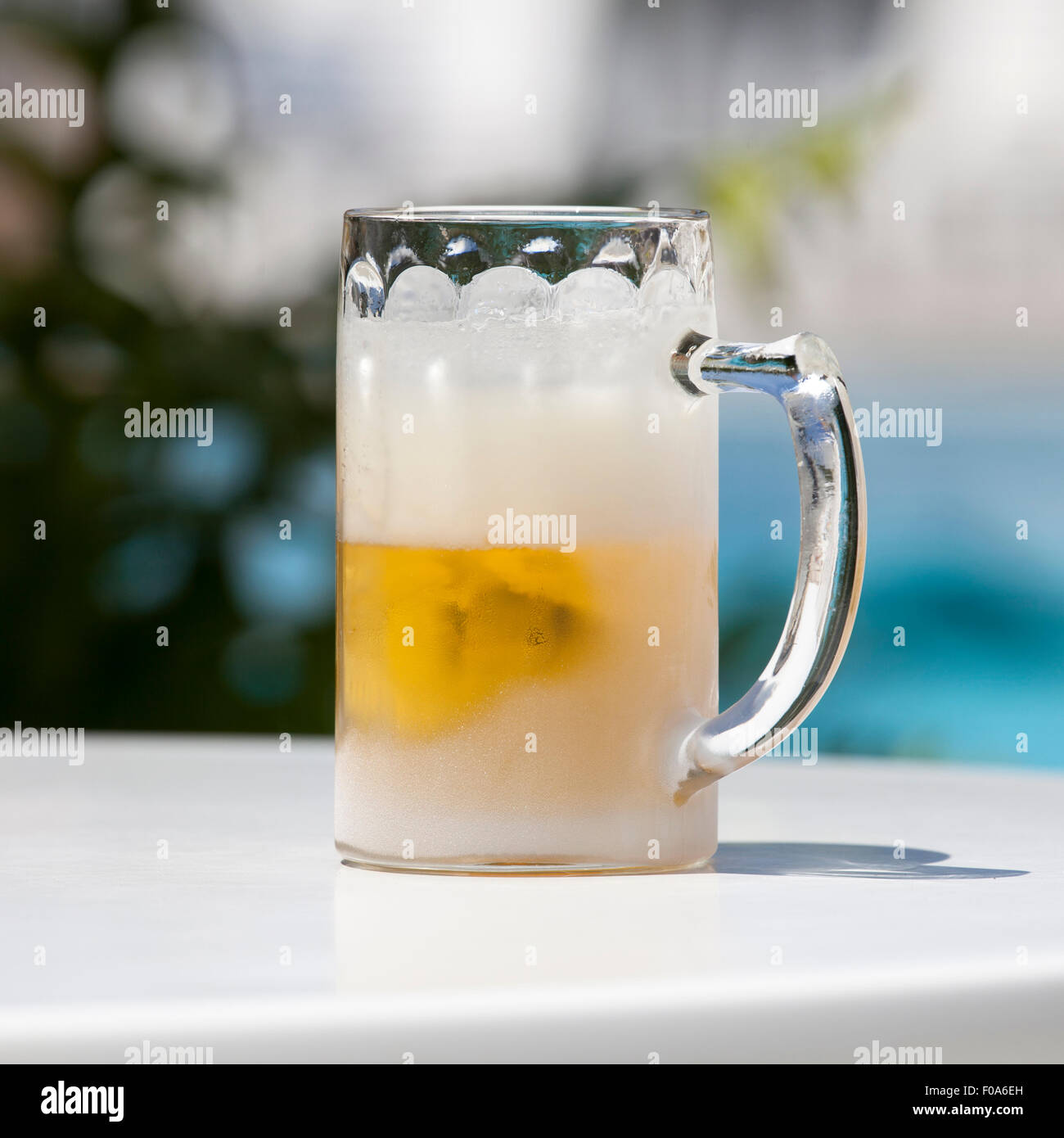 Extremely cold glass with beer on a table in a very hot summer day. Image with clipping path. - Stock Image