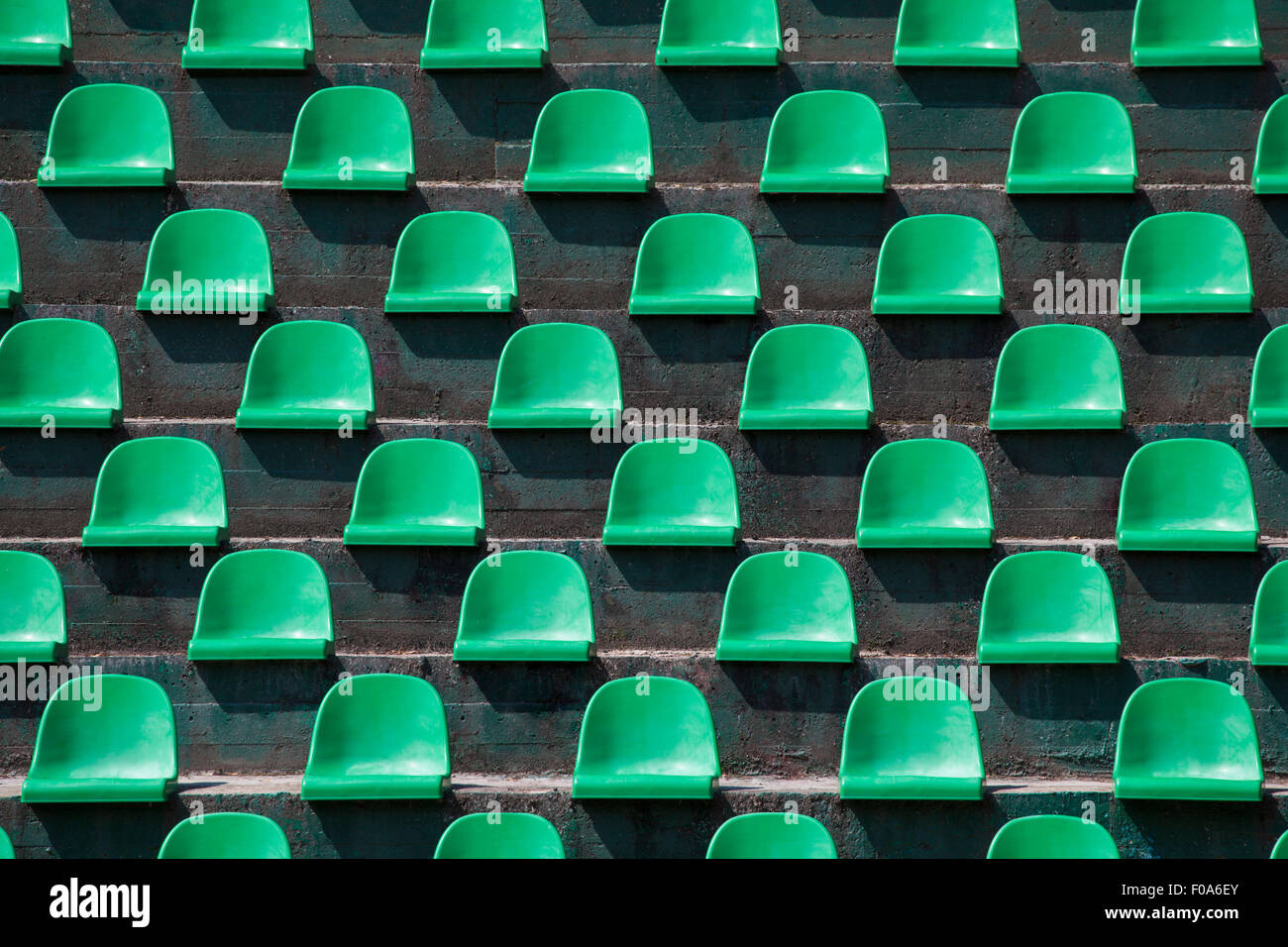 Image of green plastic stadium seats in rows. The seats are filled the frame as background. This is a day shot of - Stock Image