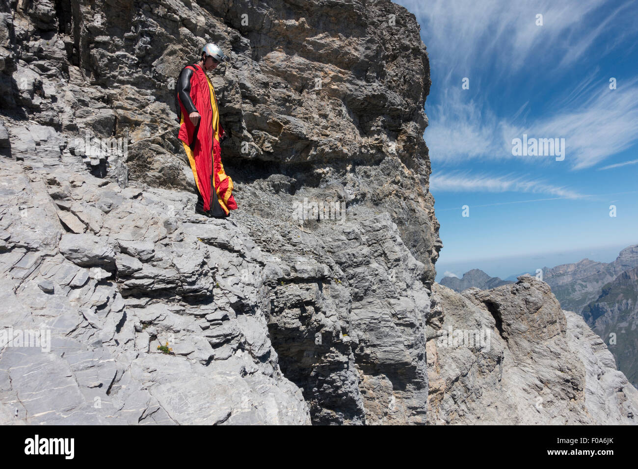b43a859f275 Wingsuit BASE jumper is getting ready to jump off a cliff and checking the  altitude by facing downward   adjusting his wings.