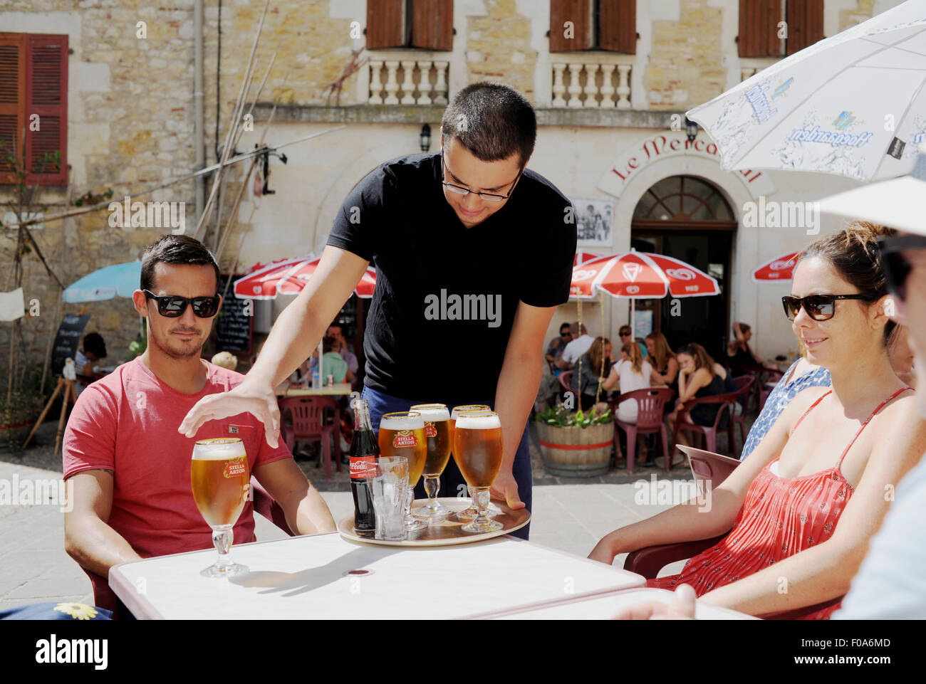 Waiter serving up Stella Artois cold beers to tourists at Puy-l'Eveque  a small town in France situated in - Stock Image