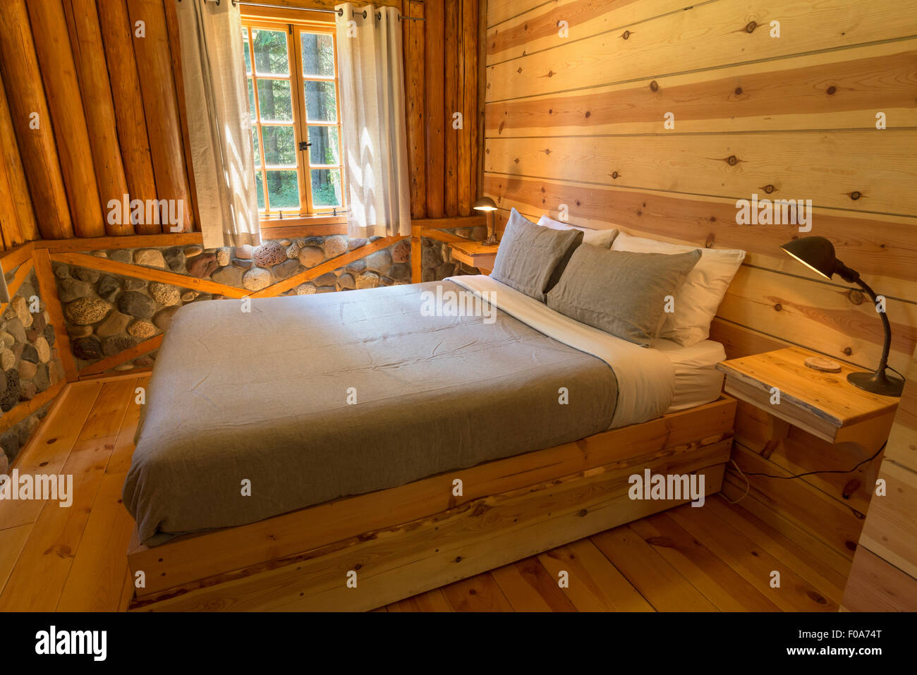 Bedroom of a log cabin at Minam River Lodge in Oregon's Wallowa Mountains. - Stock Image