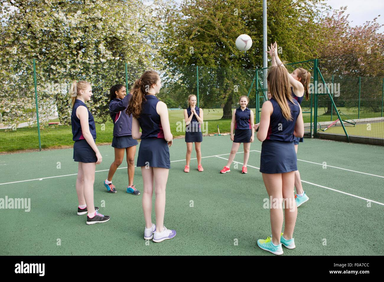 Group of students playing netball in court - Stock Image