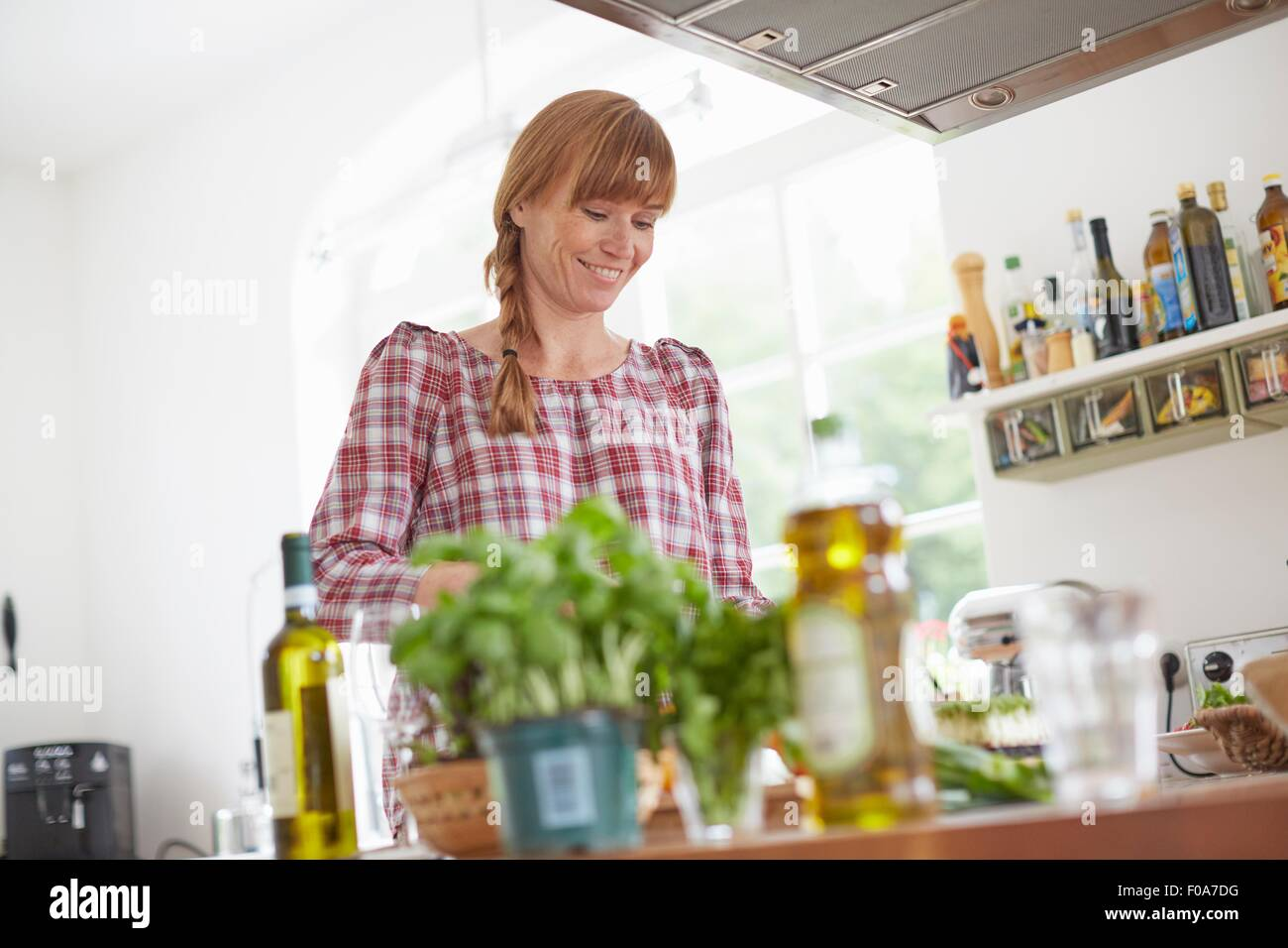 Woman preparing meal in kitchen - Stock Image