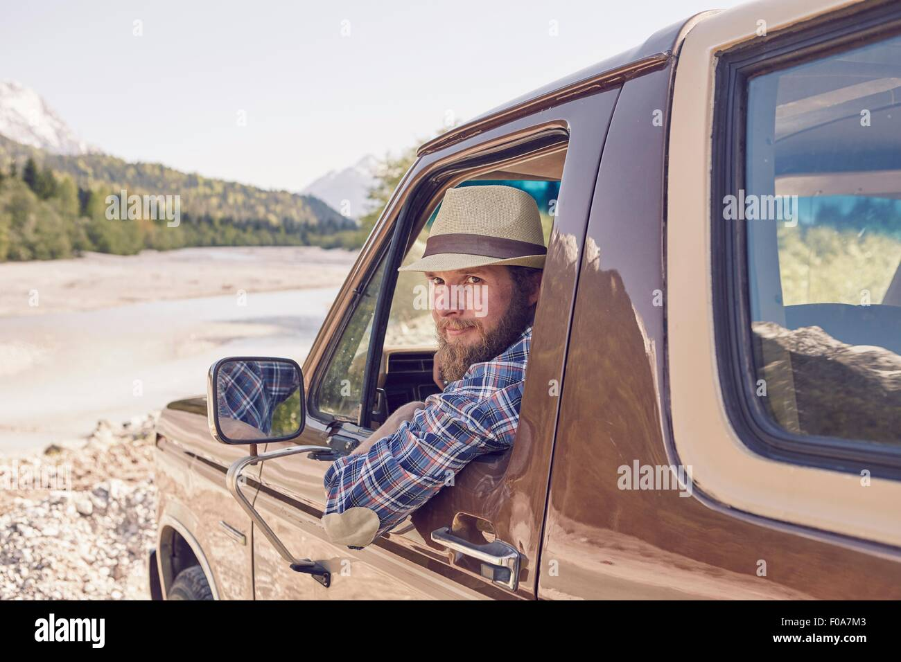 Mid adult man sitting in truck, leaning out window, looking at camera - Stock Image