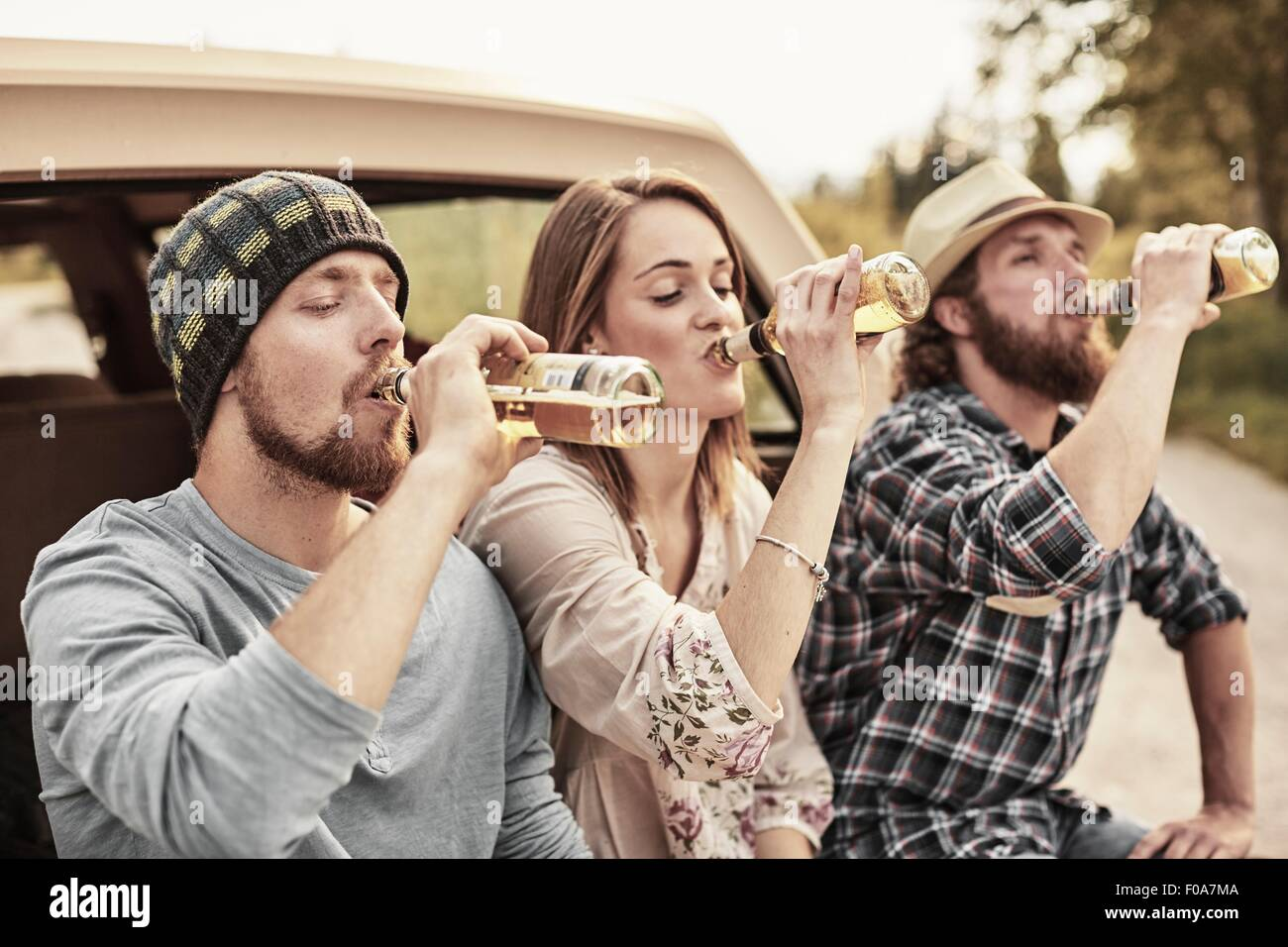 Three people drinking bottled beer in unison - Stock Image