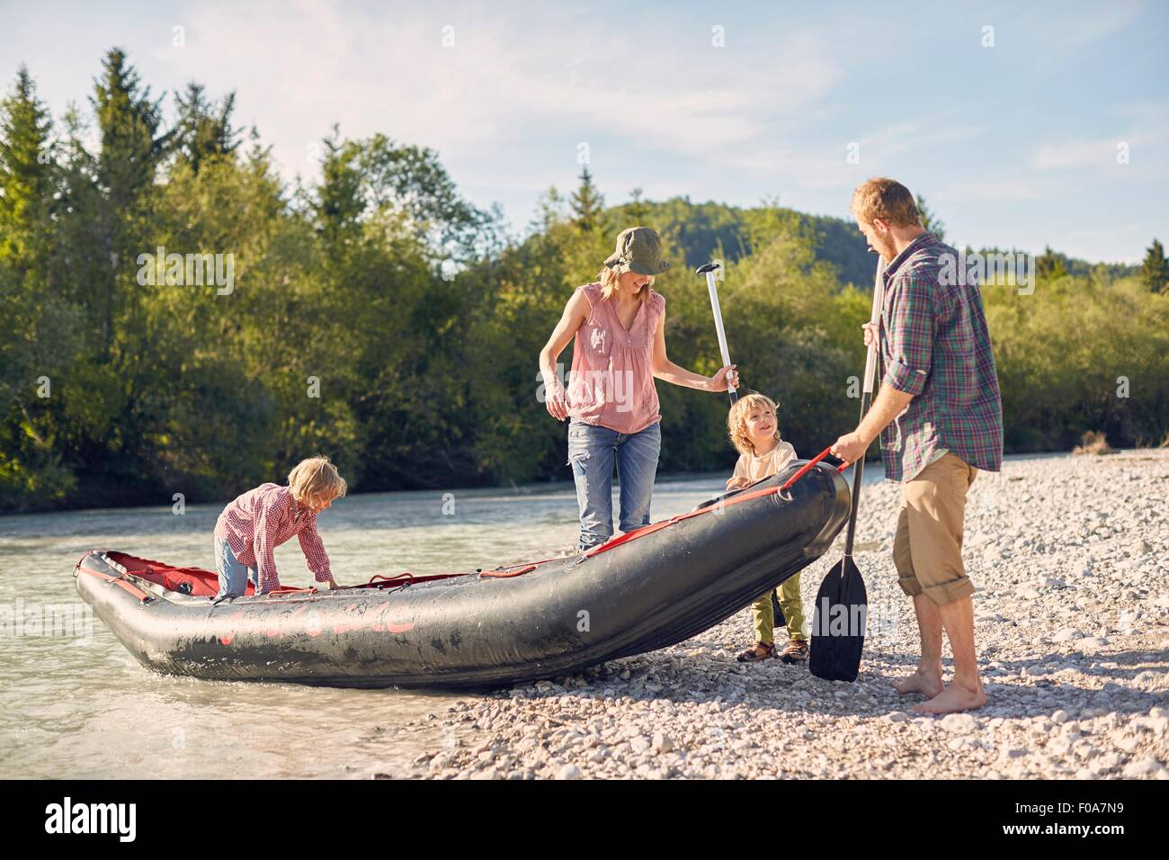 Family pulling dinghy onto riverbank, holding paddle boards - Stock Image