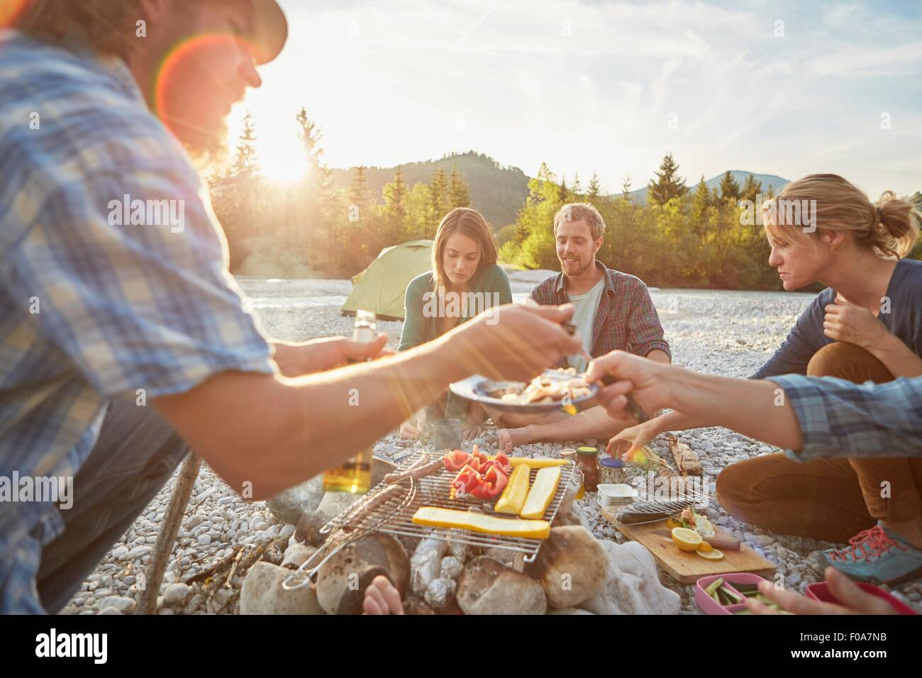 Adults sitting around campfire serving food from barbecue - Stock Image