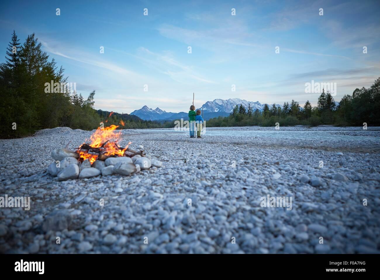 Rear view of boys near campfire holding sticks, Wallgau, Bavaria, Germany - Stock Image