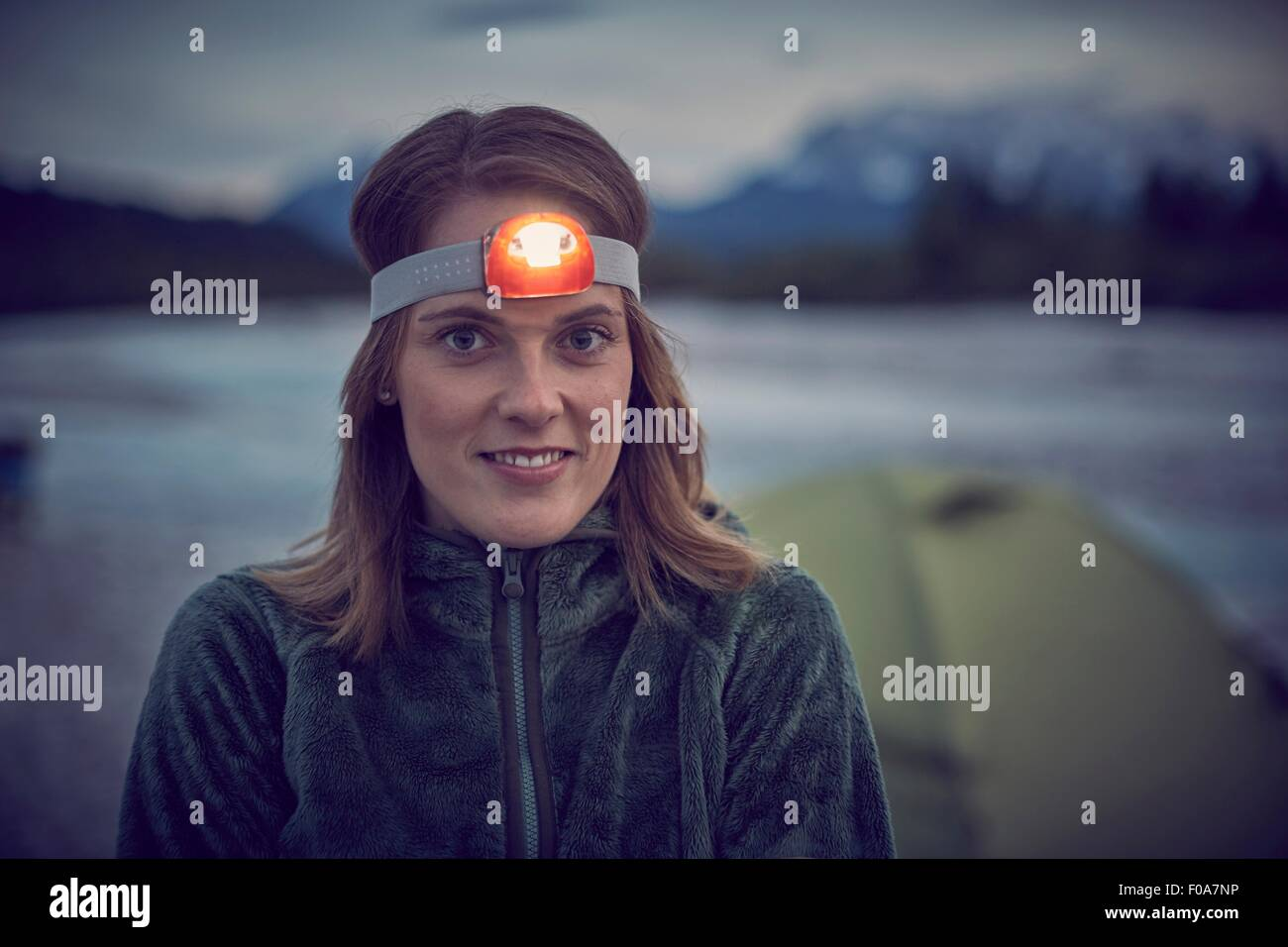 Portrait of young woman wearing headlamp, looking at camera - Stock Image