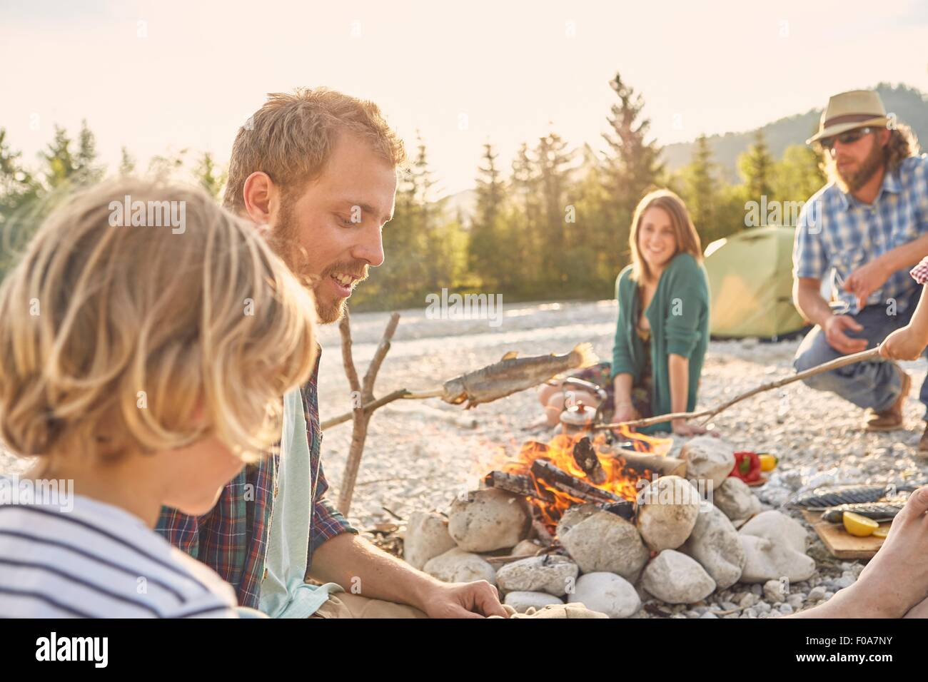 Family sitting around campfire cooking fish attached to branch - Stock Image