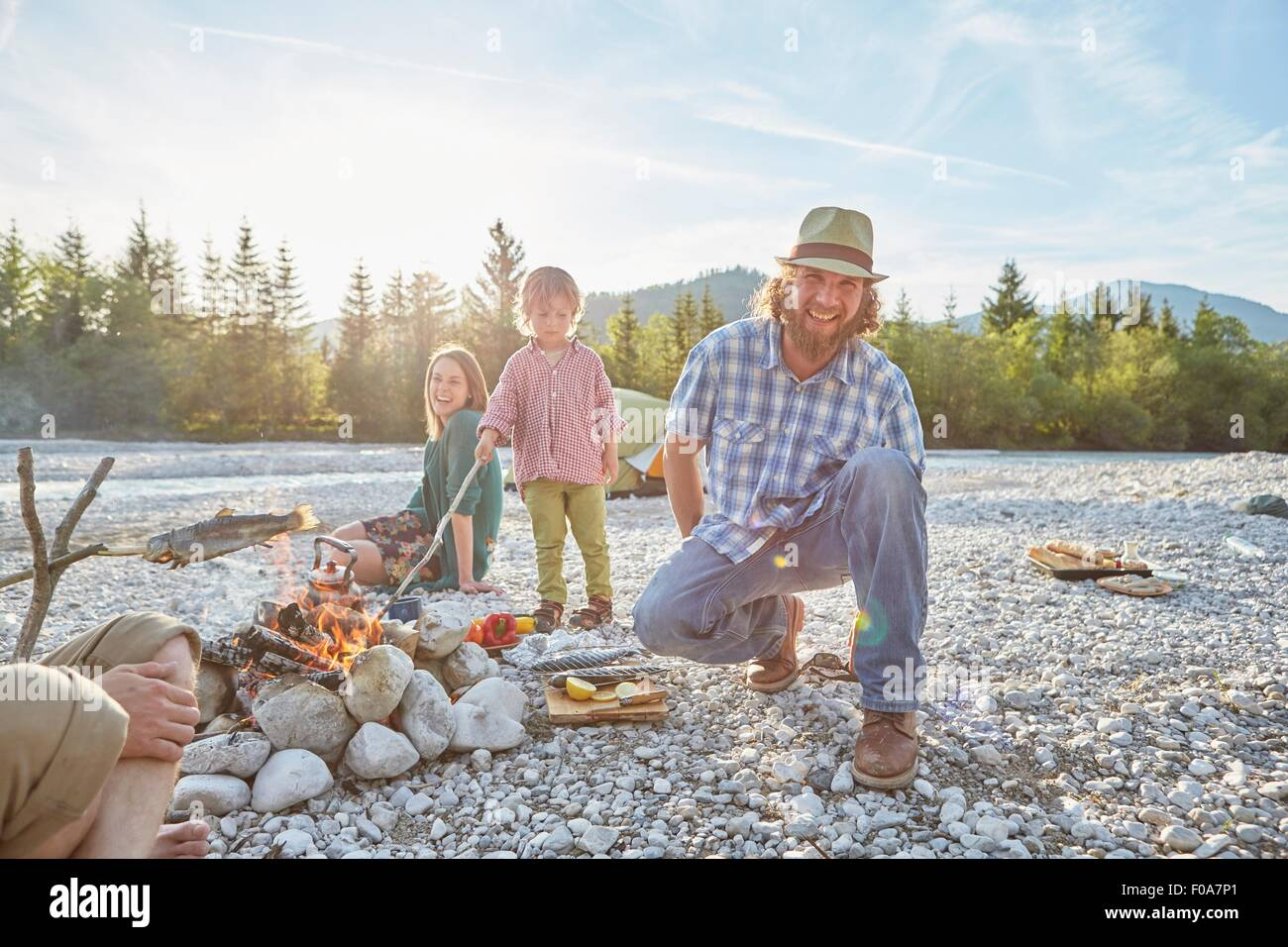 Mid adult man crouching next to campfire wearing hat, looking at camera, smiling - Stock Image