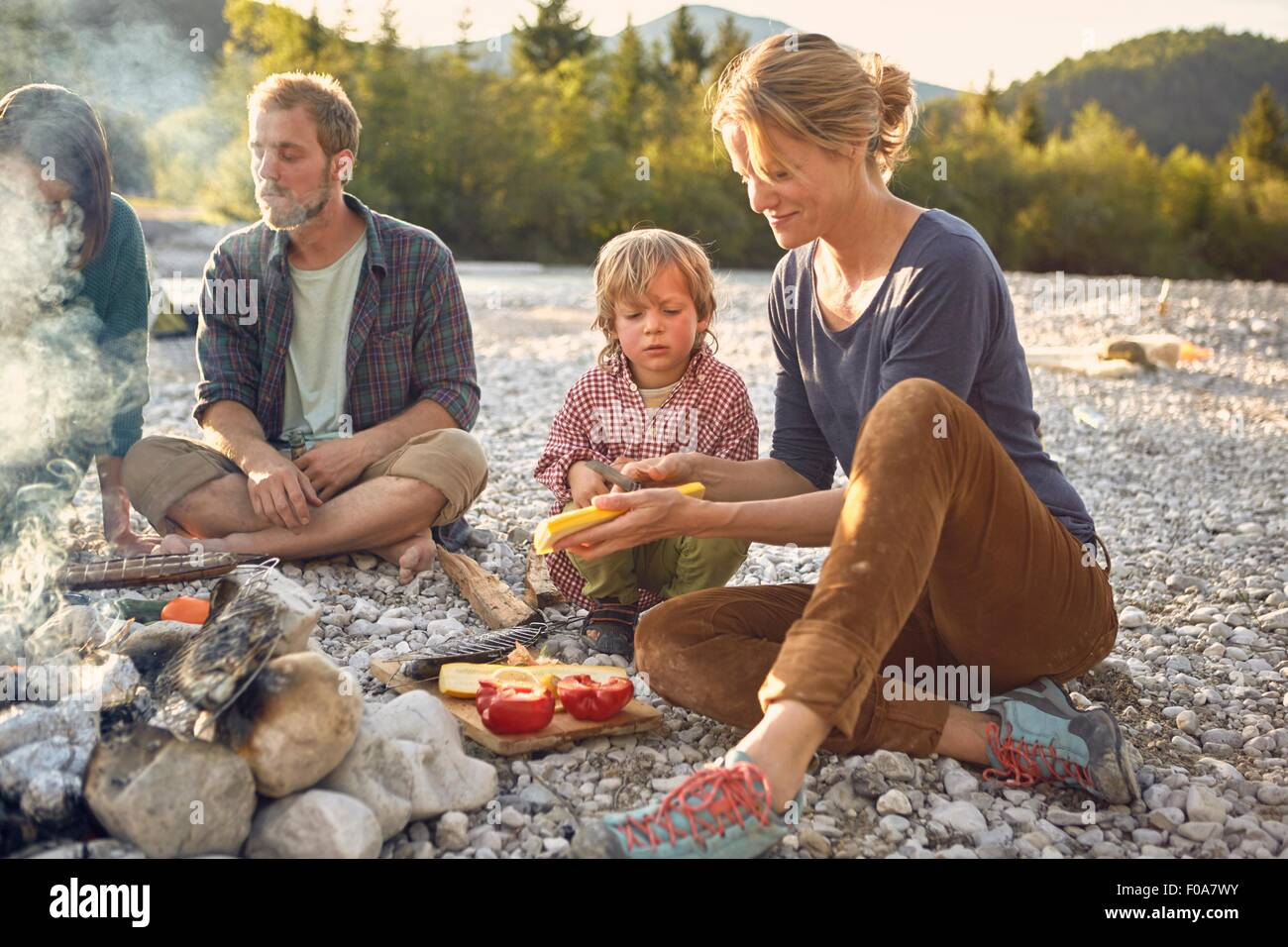 Boy sitting next to campfire watching mature woman prepare food - Stock Image