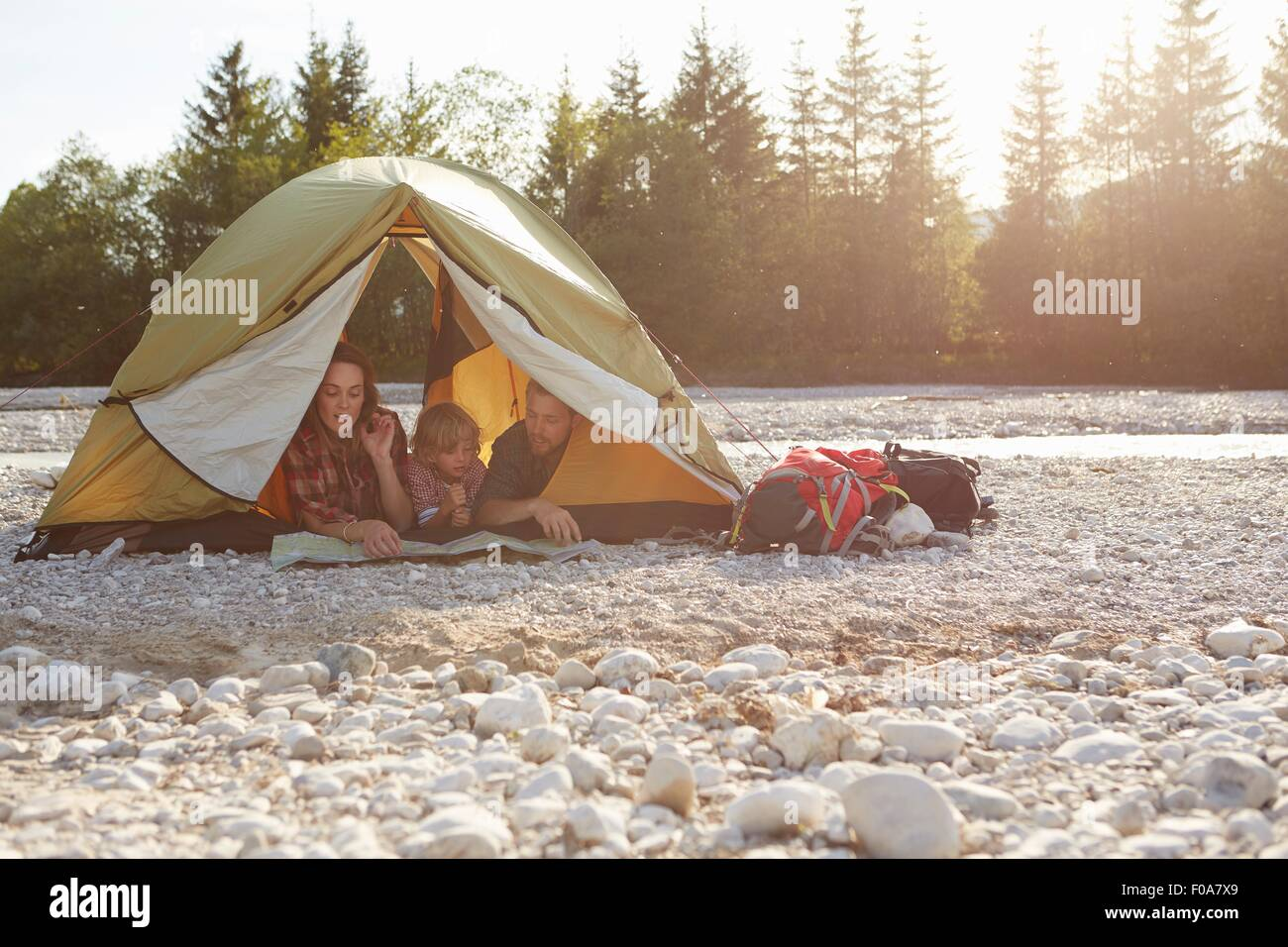 Family lying on fronts side by side in unzipped tent, looking at map - Stock Image