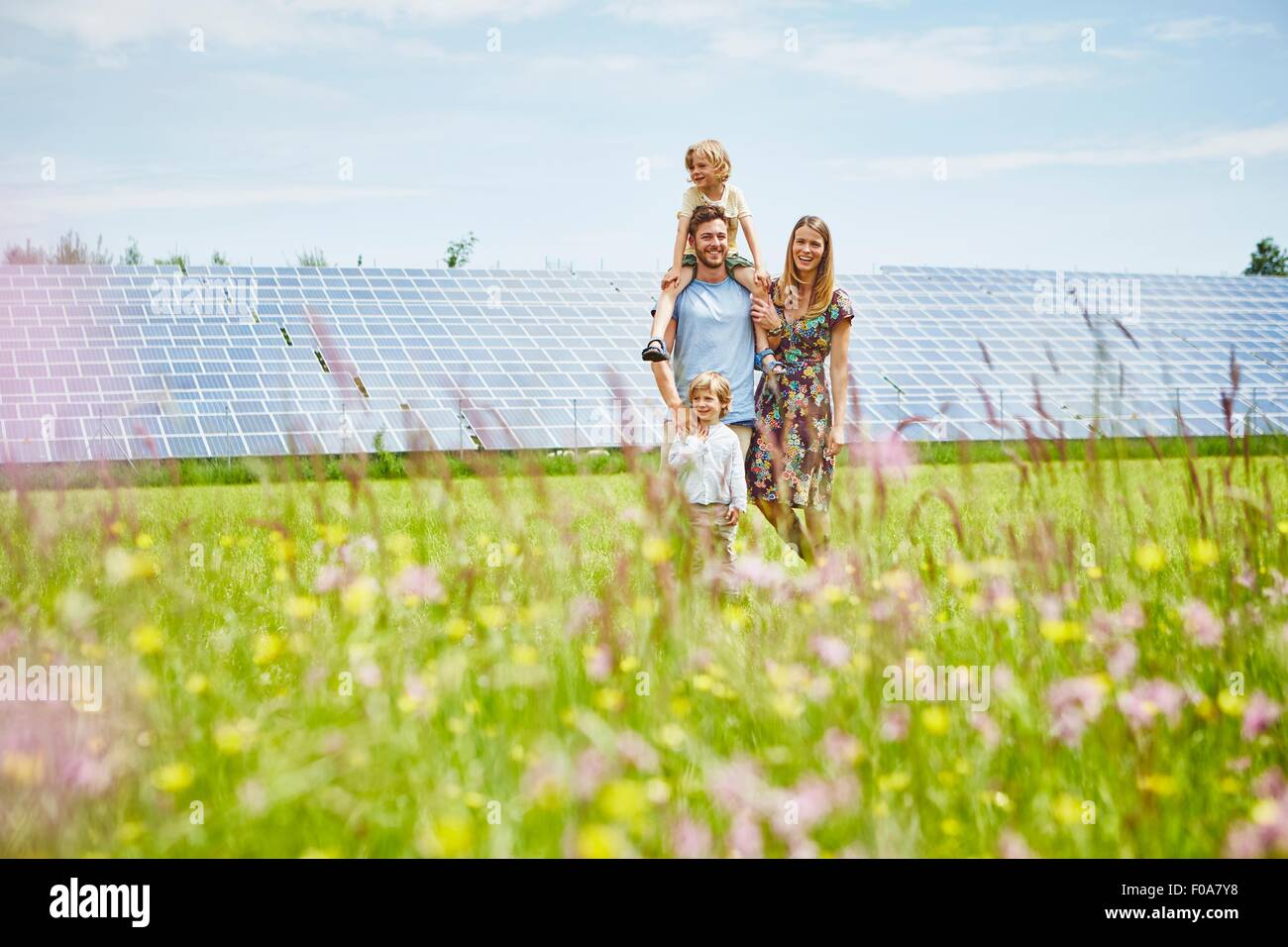 Young family, walking through field next to solar farm Stock Photo