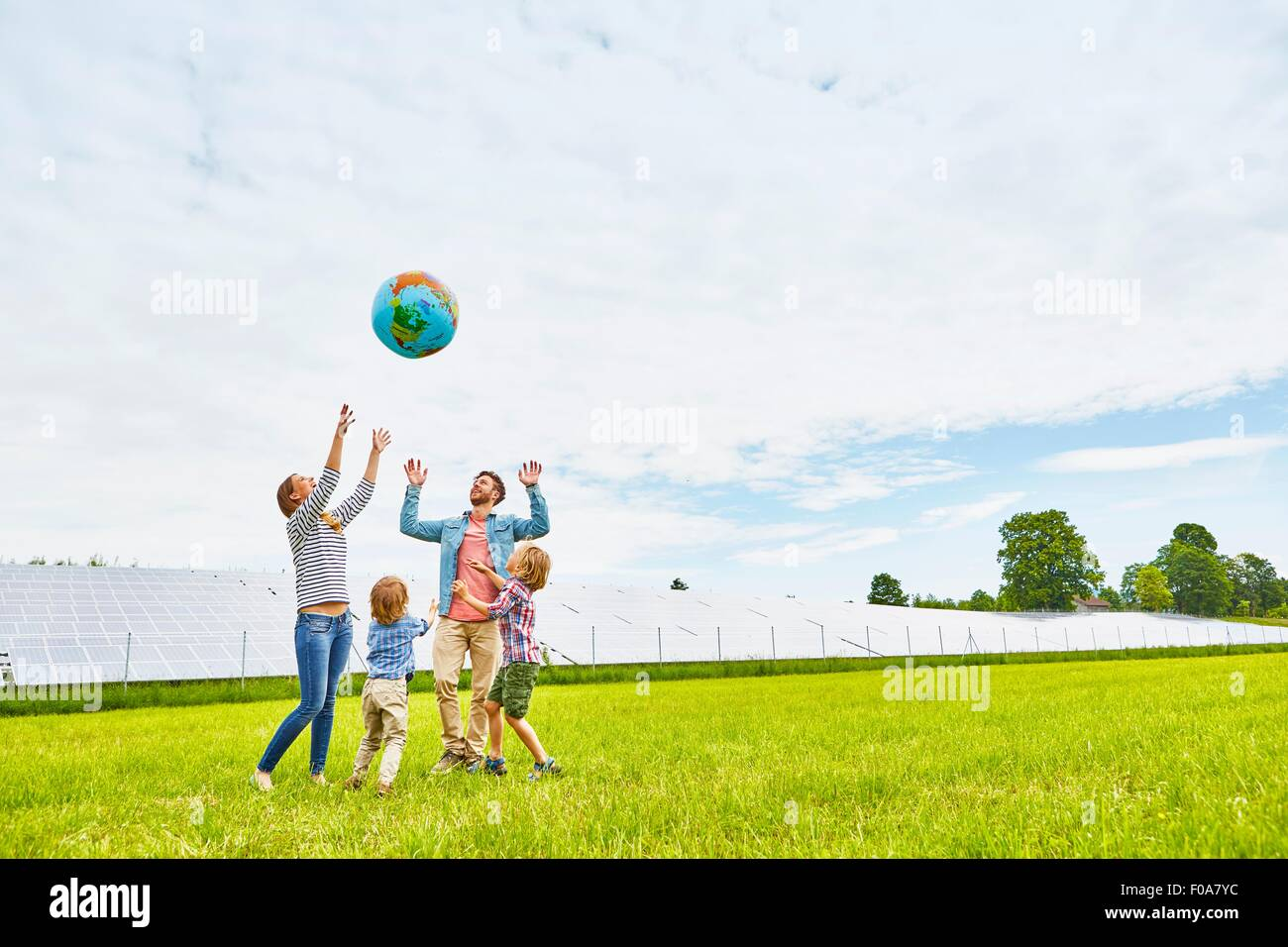 Young family playing with inflatable ball, on field, next to solar farm - Stock Image