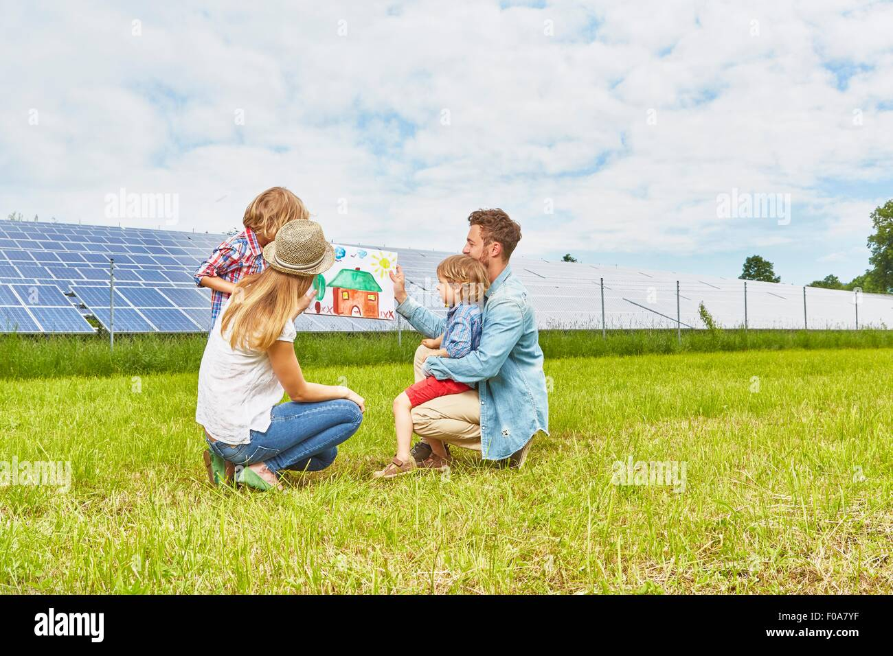 Young family sitting in field, looking at child's drawing of house, next to solar farm - Stock Image