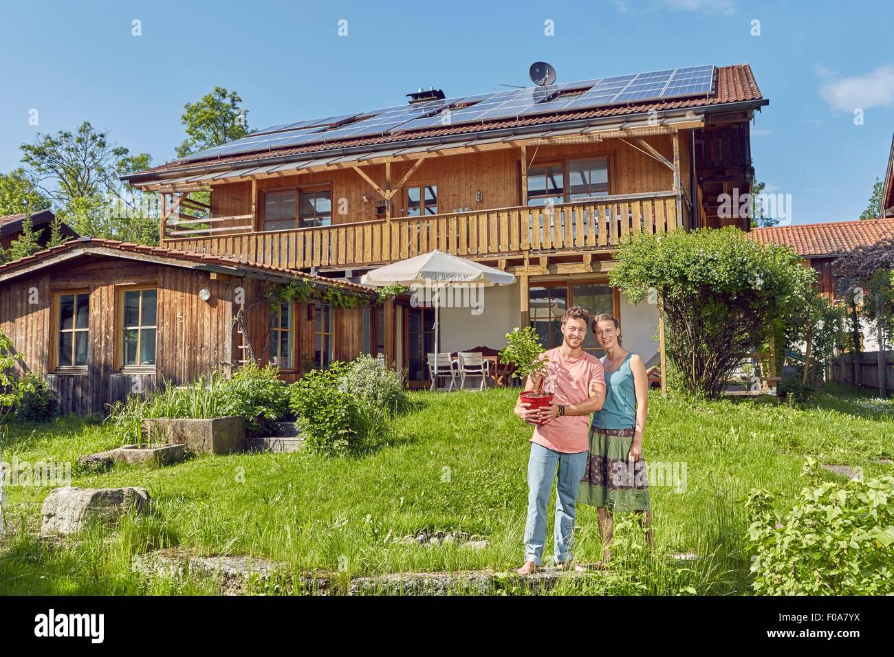 Portrait of young couple, holding pot plant, standing in front of house with solar panelled roof - Stock Image