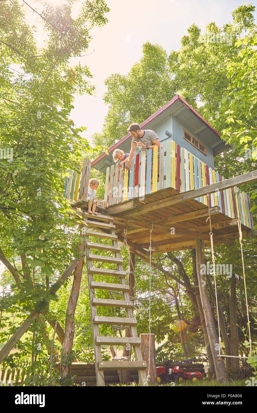 Father and two sons, painting tree house Stock Photo