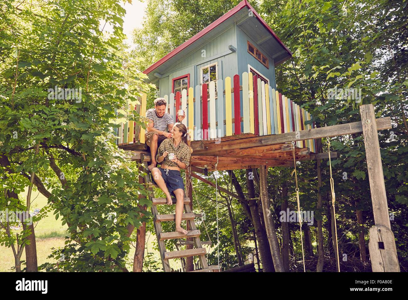 Young couple sitting on ladder of tree house - Stock Image