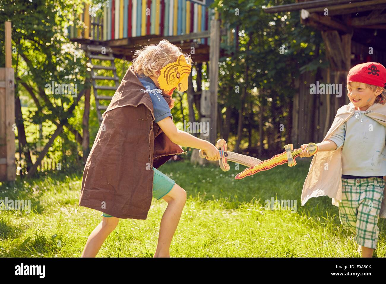 Two young brothers in garden, wearing costumes and playing with pretend swords - Stock Image
