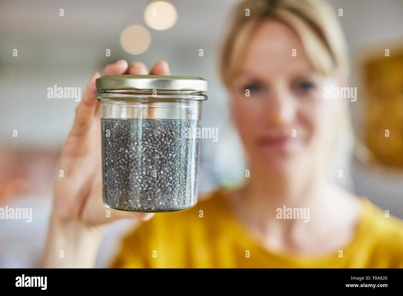 Mature woman holding up jar of seeds, focus on seeds - Stock Image