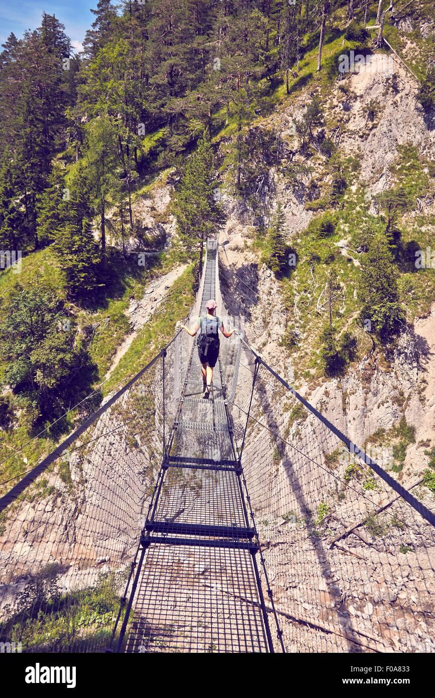 Mature woman hiking, waking along rope bridge, rear view, Karwendel-Mittenwald, Bavaria, Germany - Stock Image