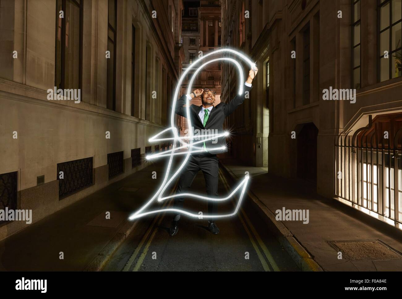 Young businessman light painting pound sterling symbol on city street at night, London, UK - Stock Image