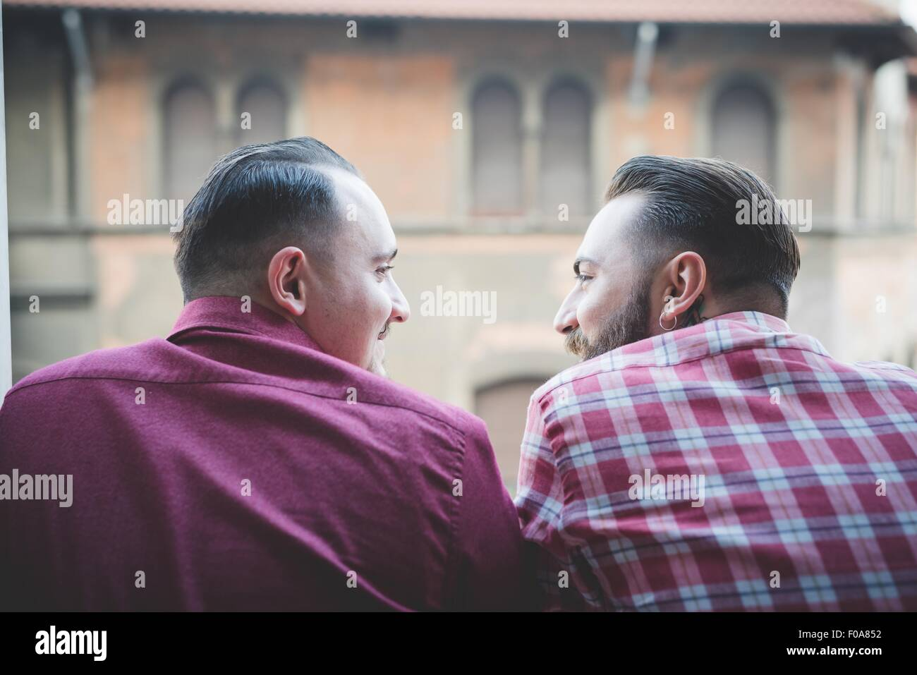 Gay couple looking out of window - Stock Image
