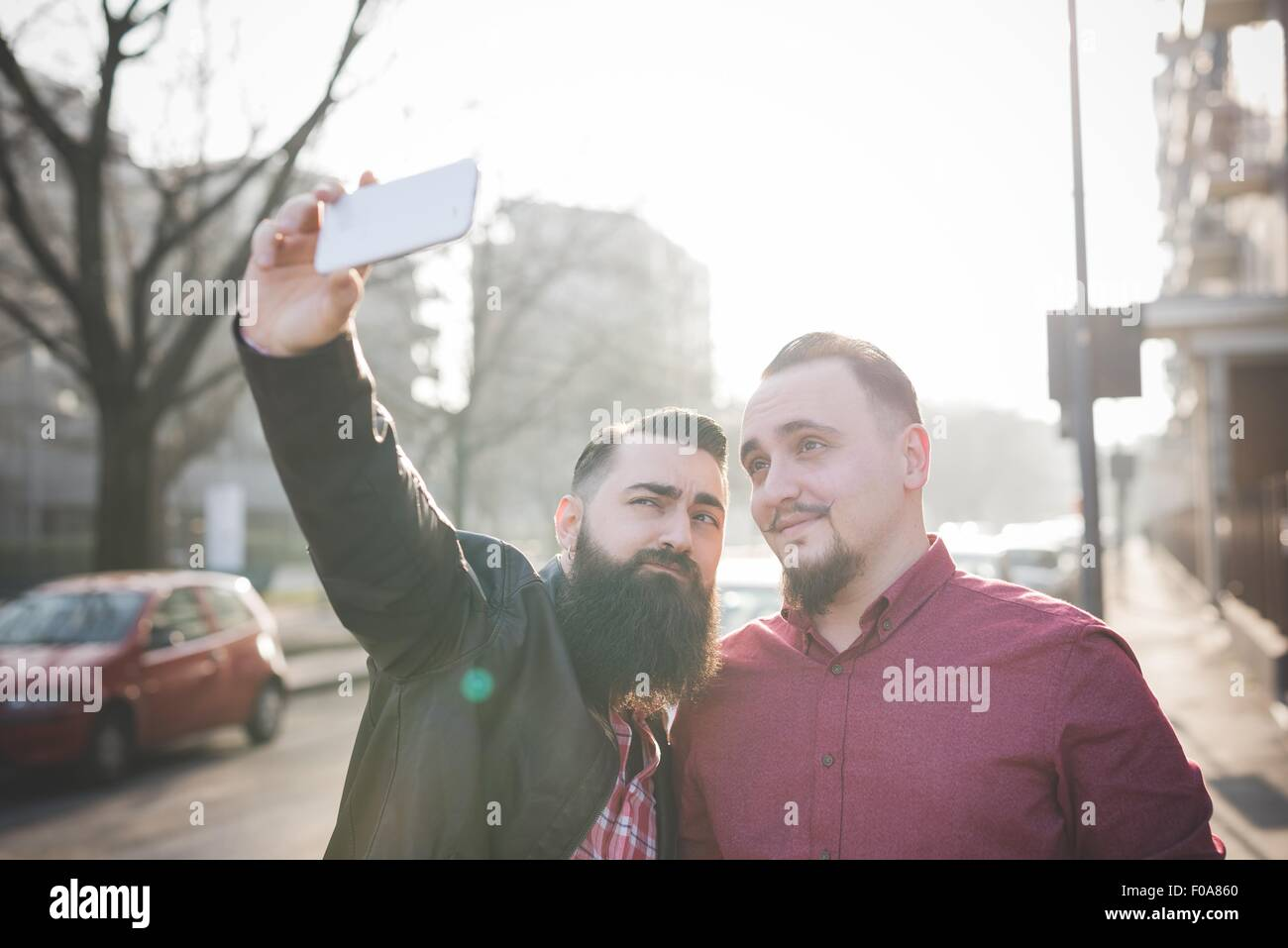 Gay couple taking selfie on pavement - Stock Image