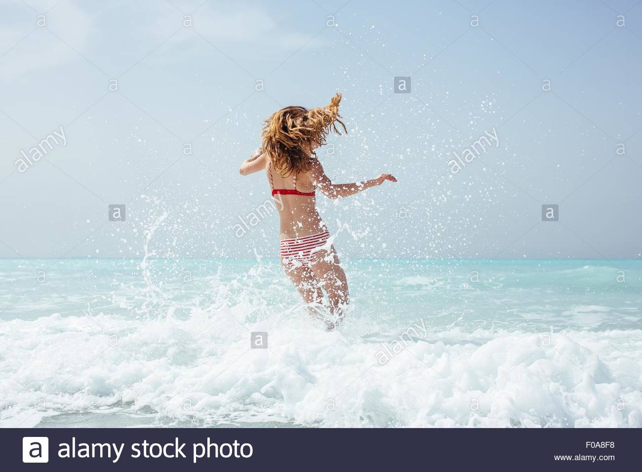 Rear view of young woman wearing bikini running in sea Stock Photo