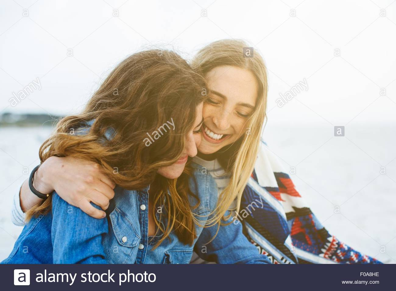 Two young female friends sitting on beach - Stock Image