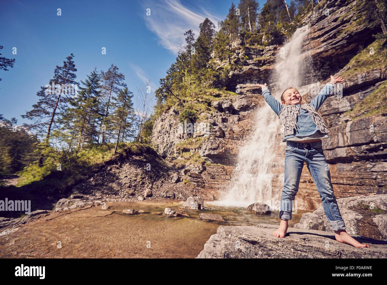 Young girl standing on rock, beside waterfall, arms raised in excitement - Stock Image