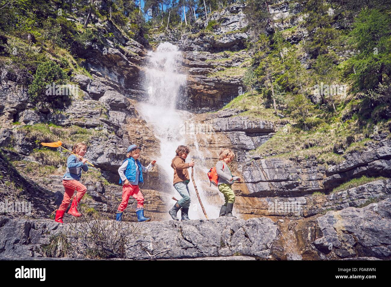 Group of children exploring by waterfall - Stock Image