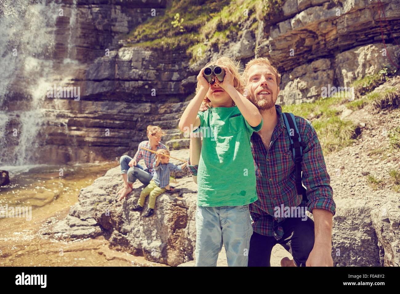 Young family exploring beside waterfall Stock Photo