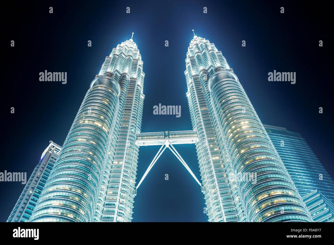 Petronas Towers, illuminated at night, low angle view, Kuala Lumpar, Malaysia - Stock Image