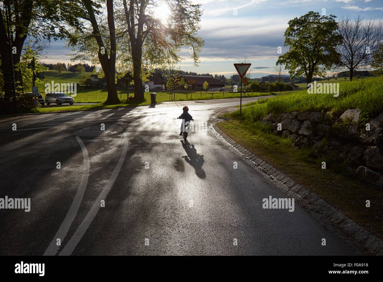 Rear silhouetted view of boy cycling on rural road - Stock Image
