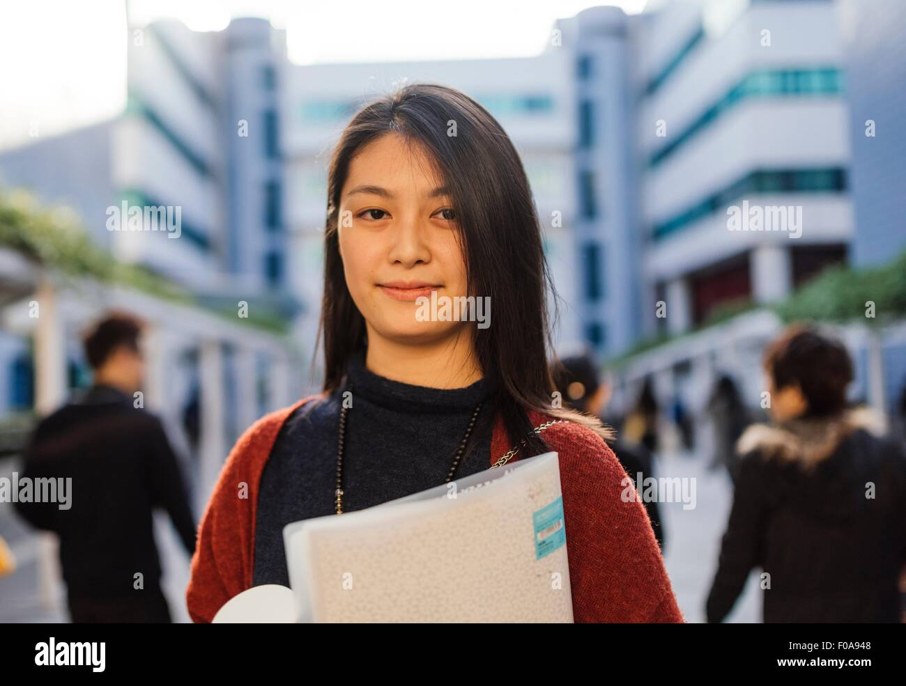 Portrait of young woman holding notebook looking at camera - Stock Image