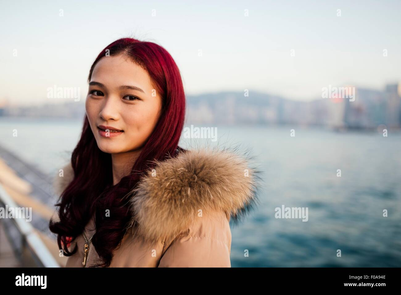 Portrait of young woman wearing fur trim coat with dyed red hair in front of water - Stock Image