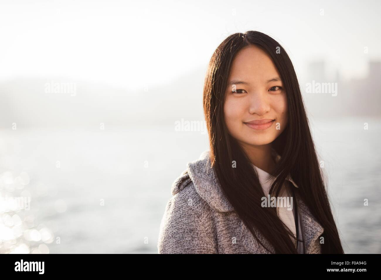 Portrait of young woman with long brunette hair in centre parting looking at camera smiling - Stock Image